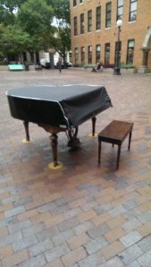 A lonely piano in a public plaza, under lock and key